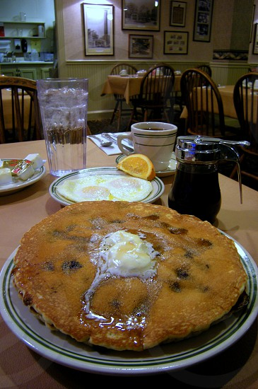 Blueberry pancakes and eggs with coffee syrup water and restaurant scene photo