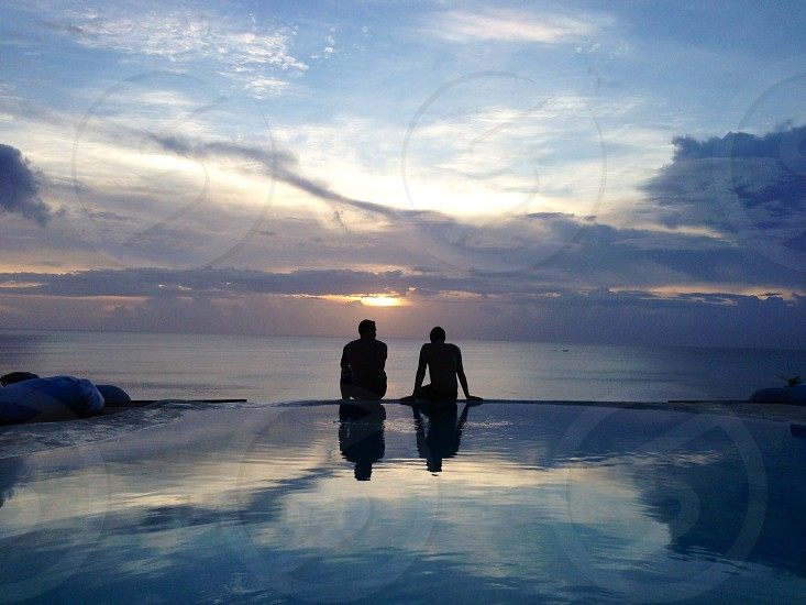 two figures silhouetted seated body of water at sunset photo