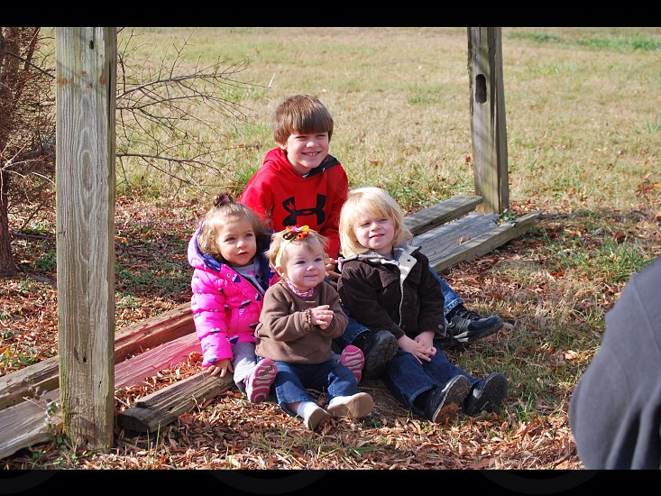 Children sitting on wood smiling photo