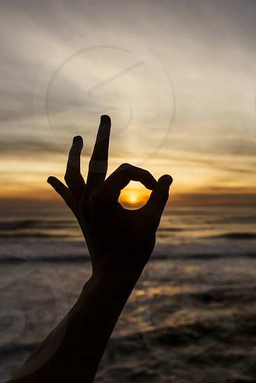 hand silhouette a okay sunset beach coast west coast warm summer happy chill relax content photo