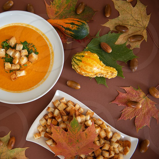 Homemade pumpkin soup with cream and crackers on autumn colors background decorated with coloful fall leavespumpkins and acorns photo