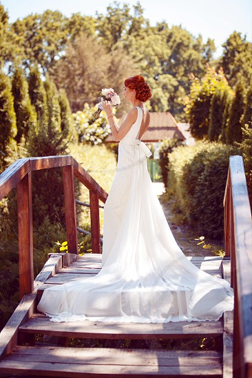 woman wearing white sleeveless bridal dress standing on brown wooden walkway near green and brown trees photo
