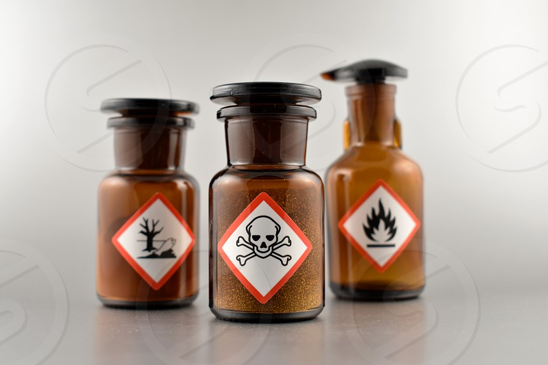 Vial with warning pictogram. Laboratory accessories. Vials on a silver background. Brown glass containers. Brown chemical glass photo