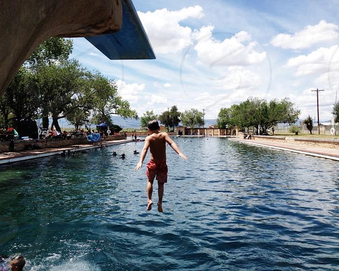 man jumping on swimming pool  photo