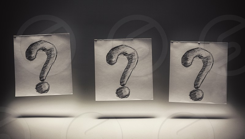 Question marks drawn on paper on gray background.  photo