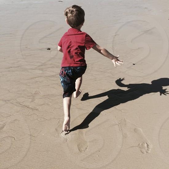 little boy running on the beach photo
