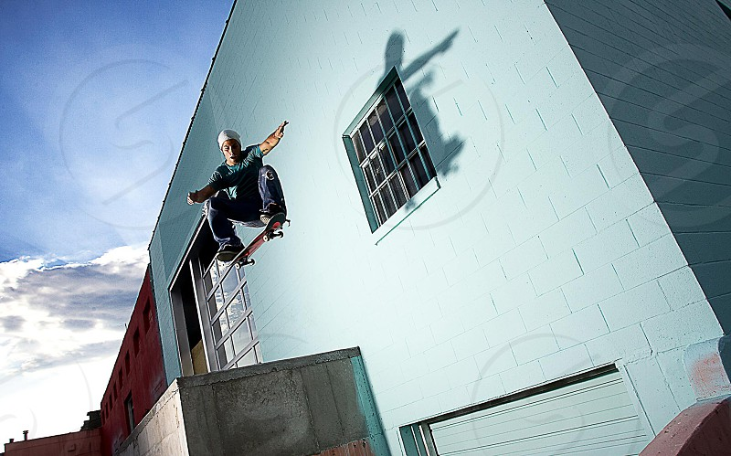 A Skateboarder jumping over a loading dock. photo