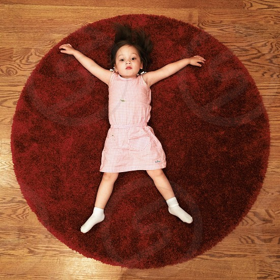 girl in pink gingham dress laying on brown round shag rug arms outstretched photo