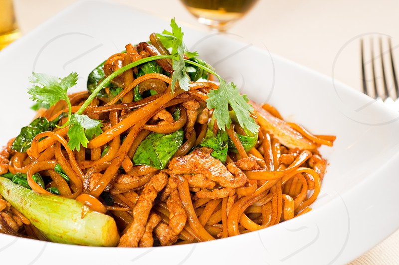 classic fresh chinese fried noodles with pork and vegetables and coriander on top photo