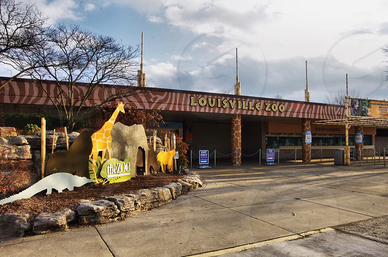 Main entrance to the Louisville Zoo with animal sculptures and ticket kiosk photo