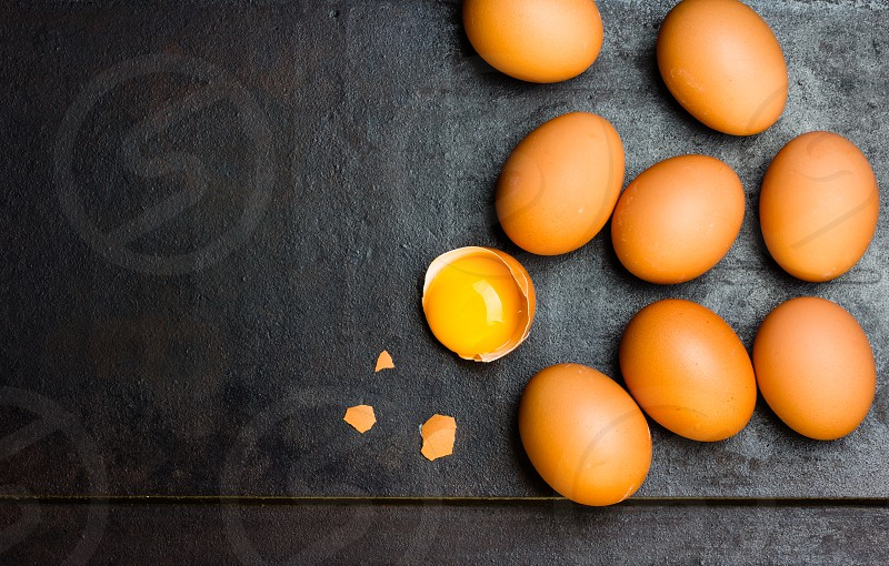Fresh eggs on black background. Top view photo