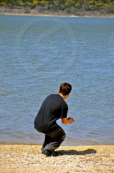 Skipping stones on the bank of a river photo