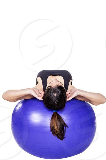Athletic and strong young woman doing some crunches on an exercise ball on a white background photo