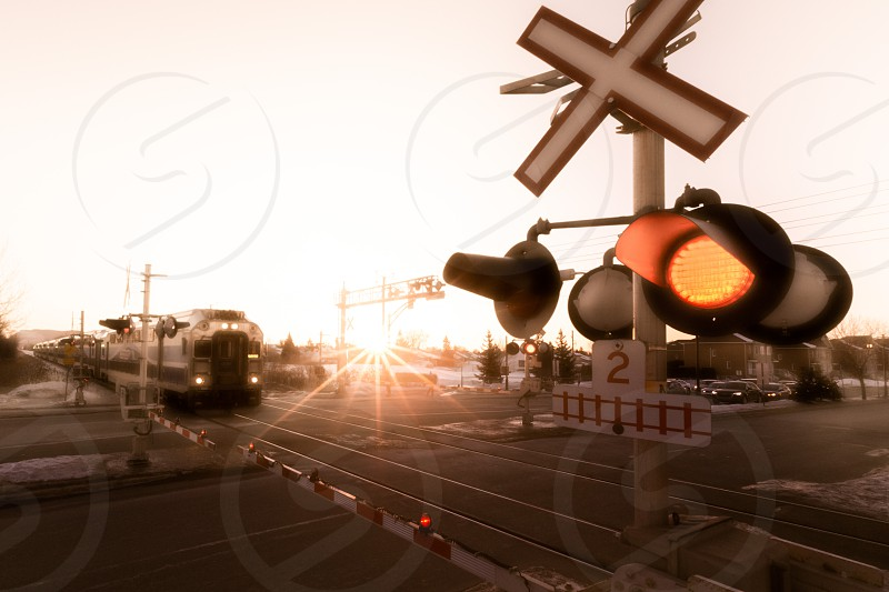 A speeding train approaching an intersection under the sunrise glow in winter near Montreal canada.  photo