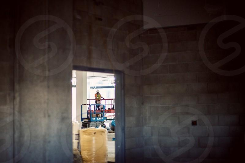 Construction worker on a scissor lift. Site yellow building concrete blocks orange blue vest hard hat. Logos altered. photo