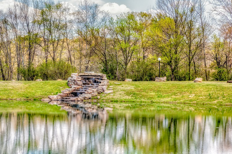 Rock waterfall and reflective lake on a beautiful spring day in a city park.  photo