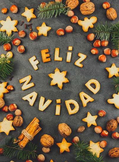 FELIZ NAVIDAD COOKIES. Words Merry Christmas en Spanish with baked cookies Christmas decoration and nuts on black slate background. Christmas card for hispanic countries top view. photo