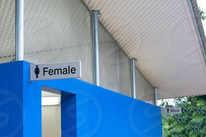 Women's bathroom sign in front of men's. photo