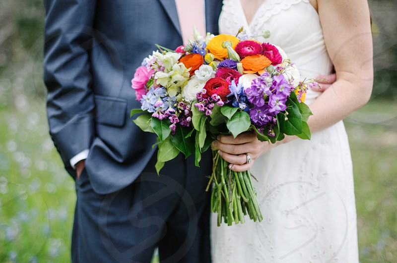 Bride and groom with colorful spring bridal bouquet  photo