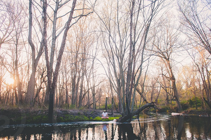 man meditating under the trees by the river photo