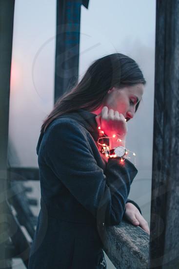 Girl standing on abridge holding red fairy lights. photo