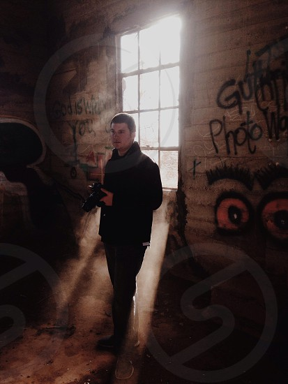 man in black clothing standing inside a graffiti covered abandoned building photo