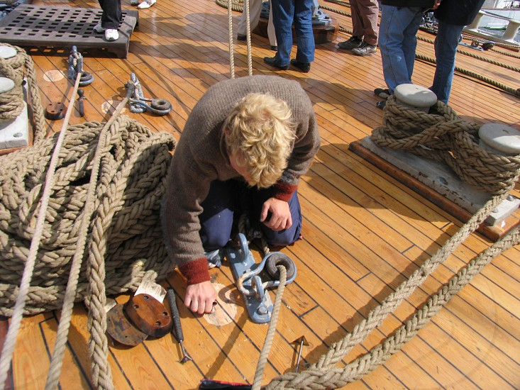Ship's deck ropes repair sailor tools wooden deck workman. photo