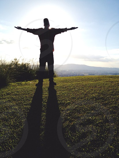 person standing on green grass with arms stretched under blue sky and white clouds photo