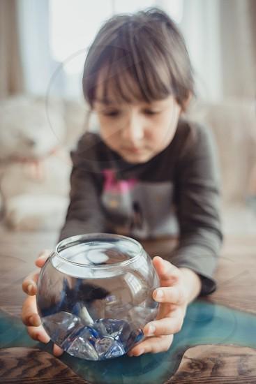 Girl with fish in round aquarium. Fish round girl home indoor look child childhood water aqua aquarium kid portrait  hands hand photo