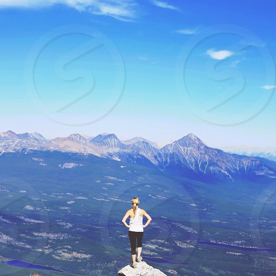 woman on top of a mountain looking over mountain ranges photo