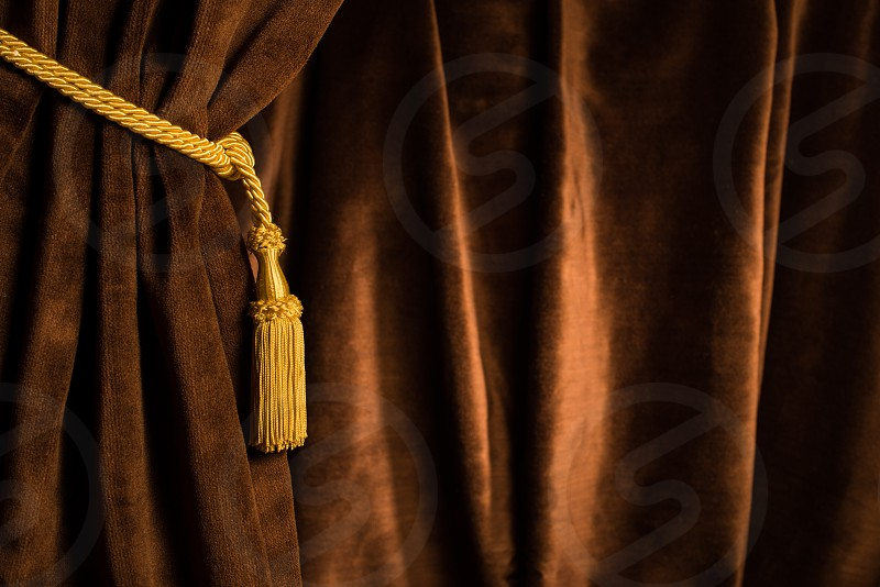 Brown theatre curtain and yellow tassels photo