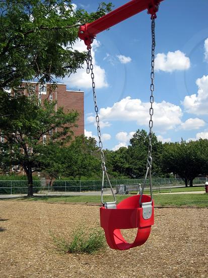 Empty red swing waiting for fun playground New York City  photo