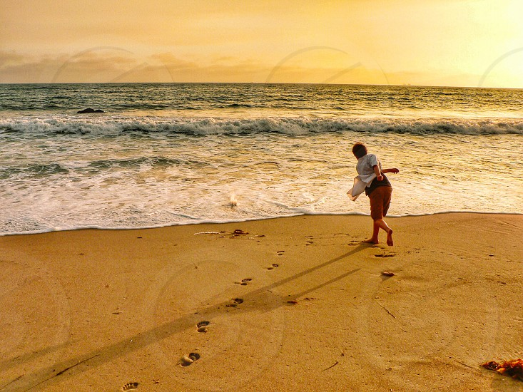 Boy rock skipping behind beach sand ocean footprints water waves action  sunset  photo