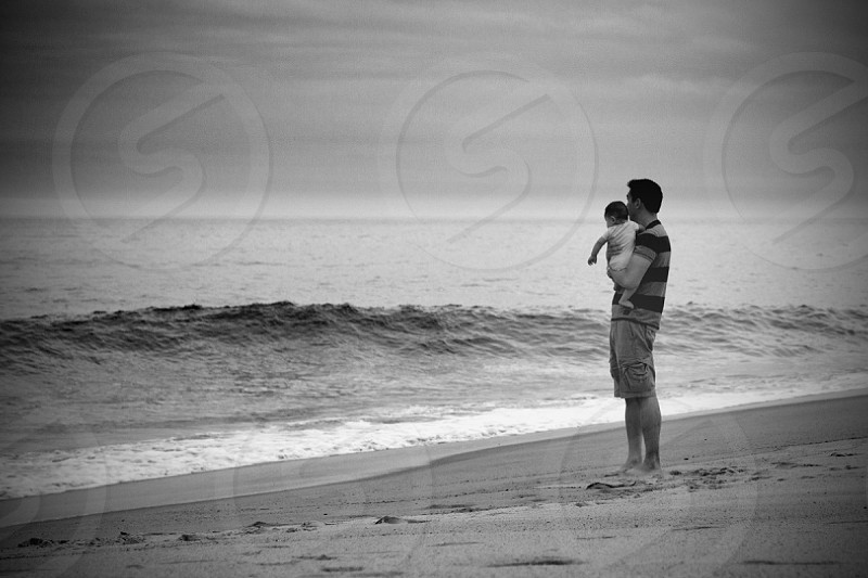 man carrying baby on seashore panoramic photography photo