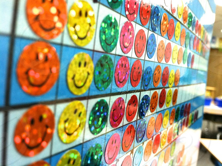 orange yellow and green smiley stickers on wall photo