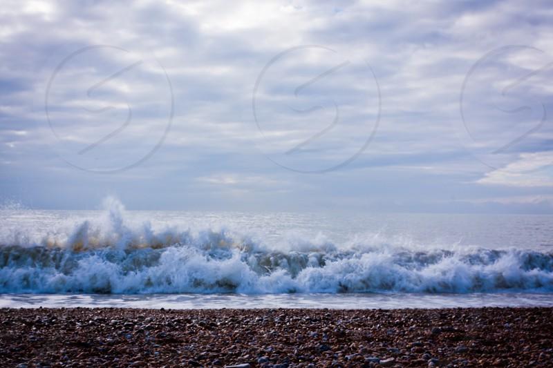 waves beach stones pebbles rocks ocean sea seaside sky clouds photo