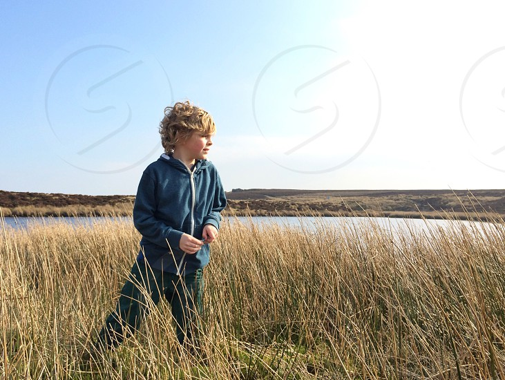 child wearing blue jacket standing in weeds photo