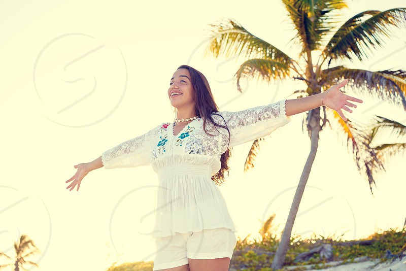 Latin beautiful girl happy open arms in Caribbean beach sand sitting relaxed photo