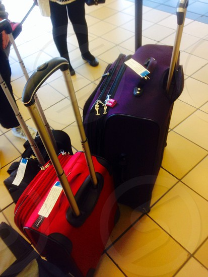 red luggage on wheels photo