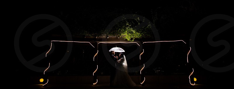 dim light newlywed couple under railings forced-perspective photo photo