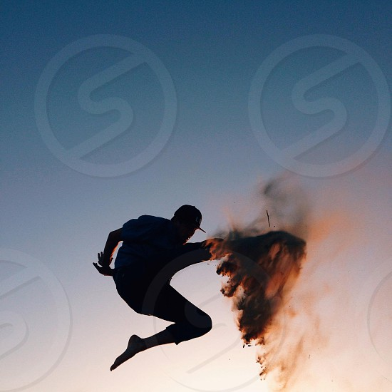 man in black fitted cap jumping on air photo