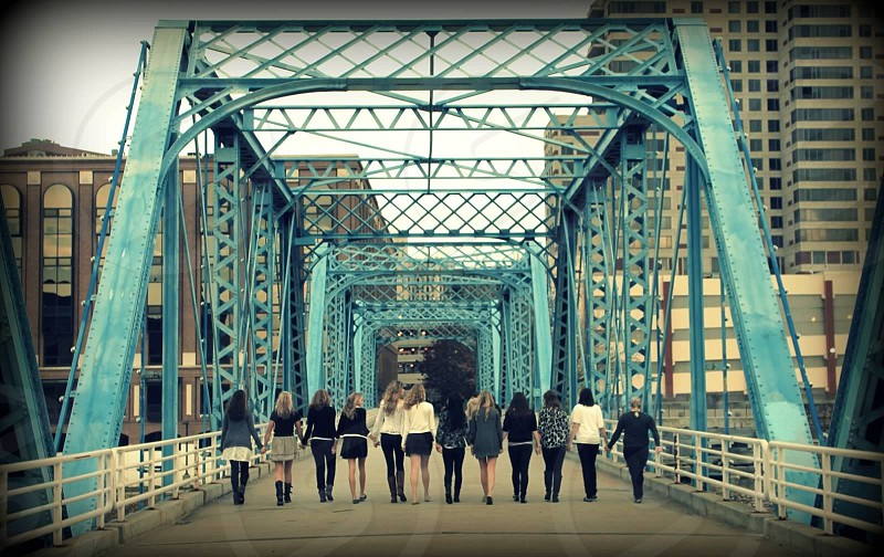 group of people standing on blue bridge photo
