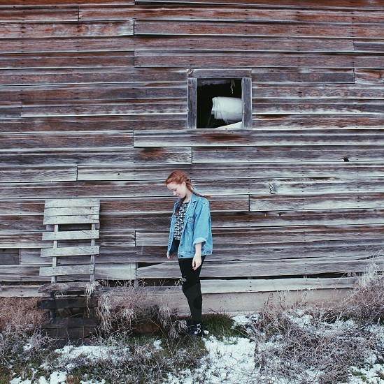 woman in blue denim jacket standing beside brown wooden wall in front of green grass photo