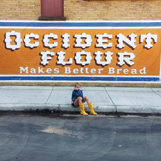 person sitting by occident flour sign photo