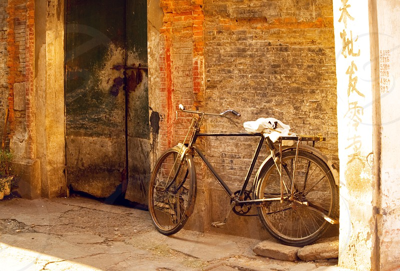 shanghai old bicycle over a brick walland old door photo