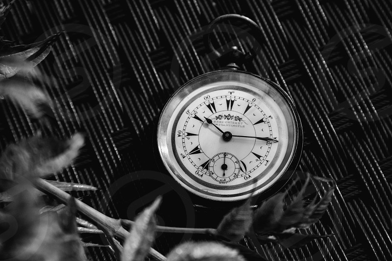 A black and white shot of an old pocket watch. photo
