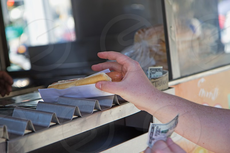 Street stall to sell hot dogs. Hand of a man holding a hot dog the other hand holding the money ready to pay. photo