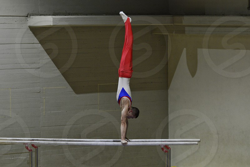man wearing white and blue tank top red pants doing gymnast exhibition photo