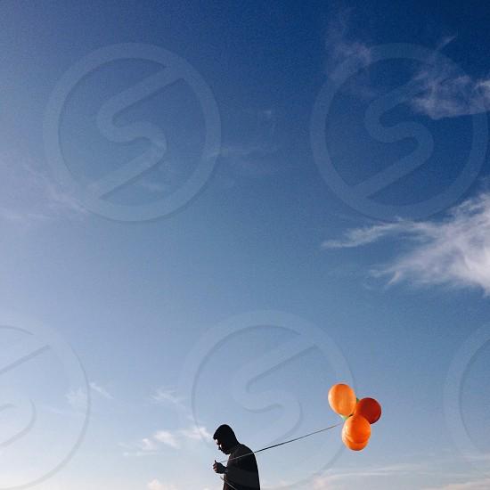 man holding string of orange rubber balloons photo