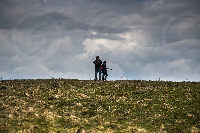 two people with backpacks on hill under gray sky photo